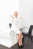 La donna di affari eccitata si tiene per mano sull'ufficio alzato Immagini Stock