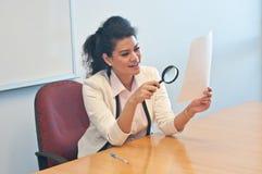 La donna di affari esamina i dettagli del contratto secondo la lente fotografia stock