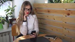 La donna di affari esamina meditatamente lo schermo dello smartphone, controllante il email stock footage