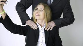 La donna di affari fa il selfie su un telefono, l'impiegato massaggia le suoi spalle e collo dopo un lavoro lungo stock footage