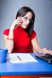 La donna di affari fa una chiamata di telefono con un computer portatile Fotografia Stock