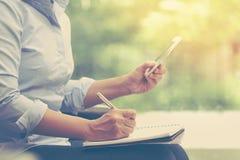 La donna di affari fa una nota ed usando il credito mobile c dello Smart Phone fotografia stock