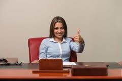 La donna di affari felice che mostra i pollici aumenta il segno fotografia stock libera da diritti