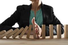 La donna di affari ferma una caduta a catena come il gioco di domino Concetto di impedire crisi e guasto nell'affare immagini stock libere da diritti