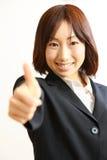 La donna di affari giapponese con i pollici aumenta il gesto Immagine Stock