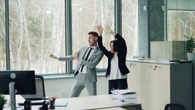 La donna di affari graziosa sta insegnando al suo collega maschio a ballare ascoltare la musica e muoversi nell'ufficio che gode  video d archivio