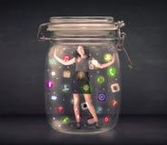 La donna di affari ha catturato in un barattolo di vetro con le icone colourful c di app Immagini Stock Libere da Diritti