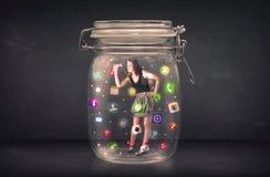 La donna di affari ha catturato in un barattolo di vetro con le icone colourful c di app Immagine Stock