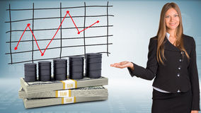 La donna di affari indica la mano sui barilotti lubrifica e soldi Immagini Stock Libere da Diritti