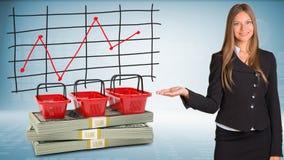 La donna di affari indica la mano sui sacchetti della spesa e Fotografia Stock