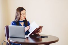 La donna di affari lavora con le note ed il computer portatile Immagine Stock