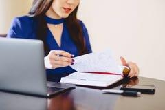 La donna di affari lavora con le note ed il computer portatile Fotografie Stock Libere da Diritti