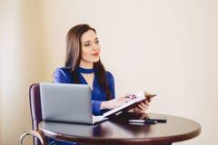 La donna di affari lavora con le note ed il computer portatile Fotografia Stock