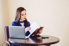 La donna di affari lavora con le note ed il computer portatile Fotografie Stock