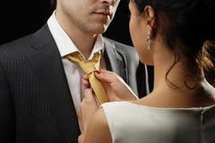 La donna di affari lega una cravatta ad un uomo d'affari Fotografia Stock