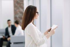 La donna di affari moderna utilizza una compressa digitale per osservare le notizie fotografia stock