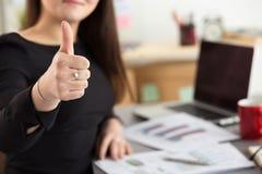 La donna di affari mostra il pollice su che si siede al suo ufficio Immagine Stock Libera da Diritti
