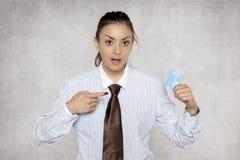La donna di affari mostra il suo dito su una carta di credito, fronte sorpreso Immagine Stock