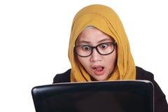 La donna di affari musulmana Working sul computer portatile ha sorpreso il gesto emozionante Fotografia Stock