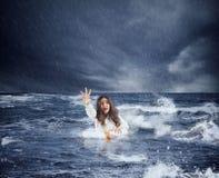 La donna di affari nell'oceano con il salvagente chiede l'aiuto durante la tempesta fotografia stock libera da diritti