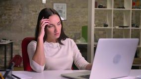 La donna di affari nell'ufficio davanti al computer portatile, si adagia su una sedia con un senso di irritazione e del disturbo video d archivio