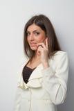 La donna di affari parla sul contac sorridente mobile dell'occhio Fotografia Stock