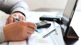 La donna di affari passa il lavoro con i grafici sul computer della compressa archivi video