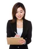 La donna di affari prende nota sulla lavagna per appunti fotografie stock
