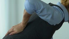 La donna di affari ritiene il dolore alla schiena acuto dopo lavoro in ufficio, stile di vita sedentario video d archivio