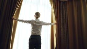 La donna di affari rivela le tende nella camera di albergo alla mattina e finestra esaminare stock footage