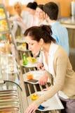 La donna di affari sceglie il buffet del pranzo del self-service Fotografia Stock