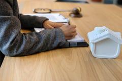 la donna di affari scrive la nota con il modello della casa fotografie stock