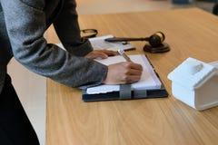 la donna di affari scrive la nota con il modello della casa fotografia stock