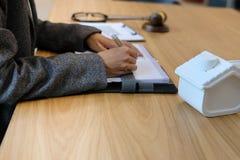 la donna di affari scrive la nota con il modello della casa fotografie stock libere da diritti