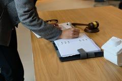 la donna di affari scrive la nota mentre esamina il contratto conside della donna fotografia stock