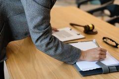 la donna di affari scrive la nota mentre esamina il contratto conside della donna fotografie stock
