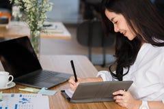 la donna di affari scrive la nota sul taccuino nel luogo di lavoro donna startup fotografie stock
