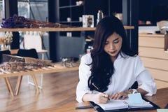 la donna di affari scrive la nota sul taccuino nel luogo di lavoro donna startup fotografia stock libera da diritti