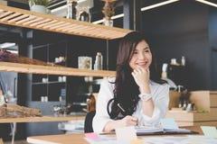 la donna di affari scrive la nota sul taccuino nel luogo di lavoro donna startup immagine stock