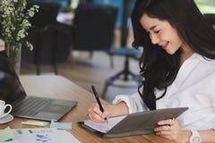 la donna di affari scrive la nota sul taccuino nel luogo di lavoro donna startup fotografia stock