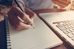 La donna di affari scrive sul taccuino con il tono dell'annata del computer portatile Fotografia Stock