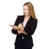 La donna di affari scrive sulla lavagna per appunti Fotografia Stock