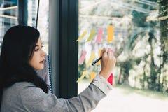 La donna di affari scrive sulle note adesive sulla parete di vetro nella riunione della r fotografia stock