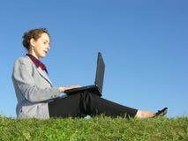 La donna di affari si siede con il taccuino su cielo blu Fotografia Stock