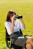 La donna di affari si siede nella ricerca piena di sole del prato binoculare immagini stock libere da diritti