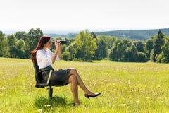 La donna di affari si siede nella ricerca piena di sole del prato binoculare fotografia stock libera da diritti
