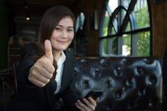 La donna di affari sorridente felice con i pollici aumenta il gesto che esamina la macchina fotografica che si siede su un sofà fotografia stock
