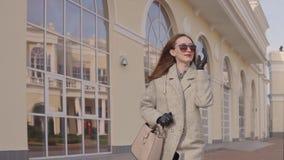 La donna di affari sta camminando per lavorare a tempo la mattina, muoventesi lungo le costruzioni video d archivio