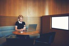La donna di affari sta leggendo il messaggio di testo sul telefono delle cellule Immagine Stock
