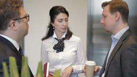 La donna di affari sta parlando con due i suoi subalterni maschii nel corridoio dell'ufficio vicino all'elevatore stock footage